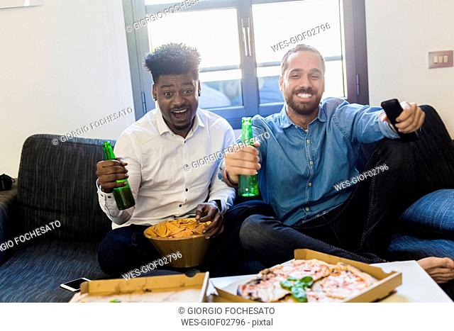 Friends with beer bottles sitting on the sofa watching TV