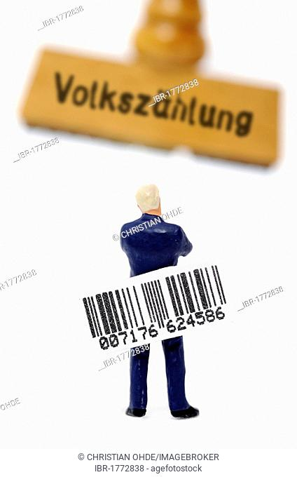 Miniature figure holding a bar code while standing in front of a stamp with the word Volkzaehlung, German for Census