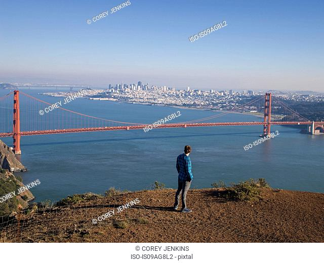 Young male tourist looking at Golden gate bridge, San Francisco, California, USA