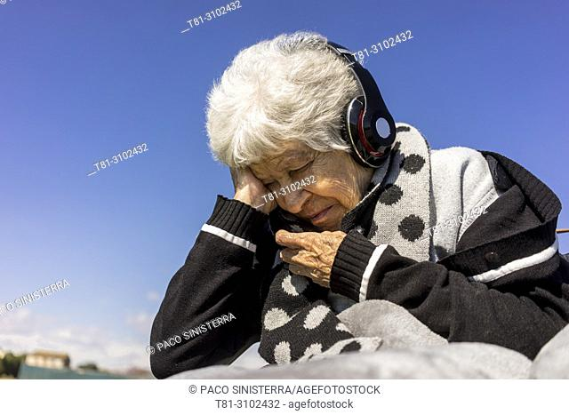 senior person listening to music with headphones, Valencia, Spain