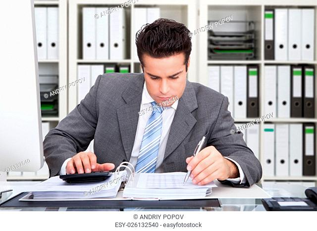 Portrait Of Happy Young Businessman Sitting At Desk Calculating Finance
