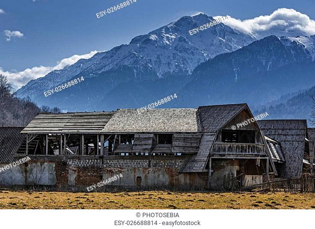 Rural scenery with old abandoned wooden farmhouse in the valley of snowy Bucegi mounains, Brasov county, Romania