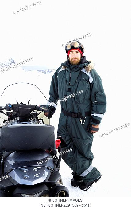 Young man standing next to snowmobile