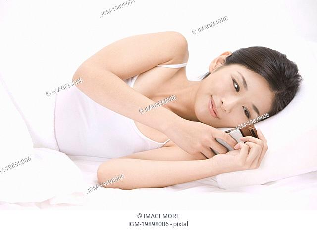 Young woman lying on bed and using mobile phone