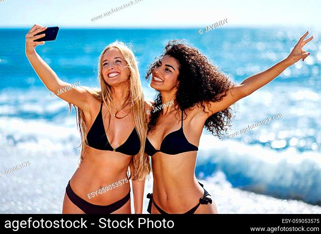 Two young women taking selfie photograph with smart phone in swimwear on a tropical beach. Funny caucasian and arabic females wearing black bikini