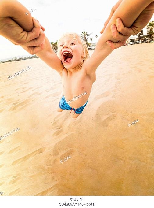 Mans hands swinging boy on Venice Beach, California, USA