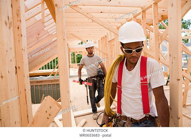 Carpenters holding power cord and level at construction site