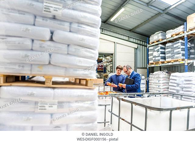 Manager and worker in storage of plastics factory checking products