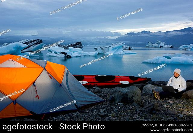 woman using her laptop at campsite by glacier lagoon