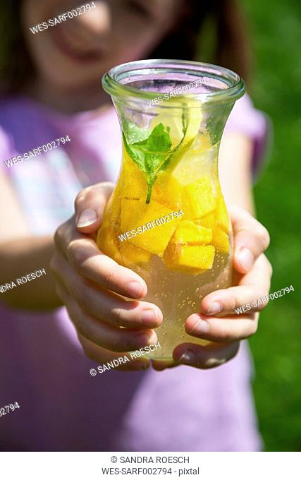 Fruit infused water with mango, lime and lemon, girl holding glass