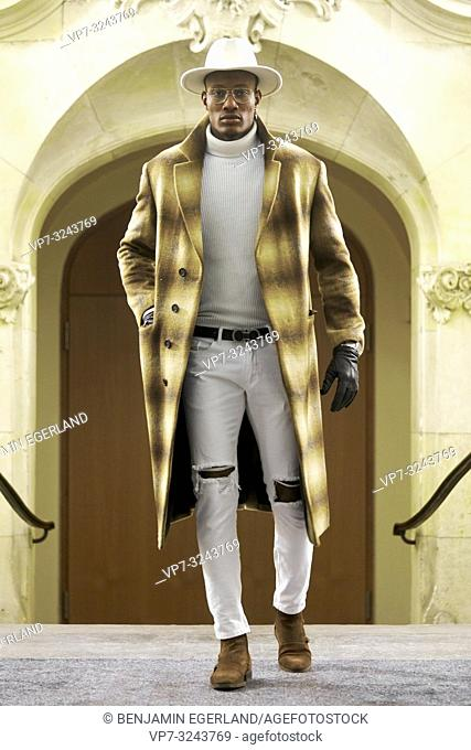 stylish wealthy man wearing expensive winter coat and fashionable men's outfit, success, in Munich, Germany