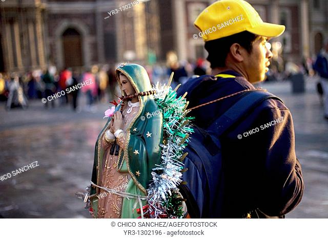 A pilgrim carries a statue of the Our Lady of Guadalupe outside the Our Lady of Guadalupe Basilica in Mexico City, December 10