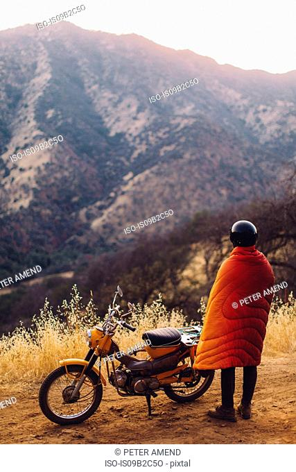 Man standing beside motorbike, wrapped in blanket, looking at view, rear view, Sequoia National Park, California, USA