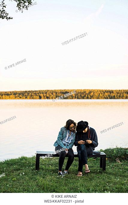 Young couple sitting on a bench near lake, checking pictures on a camera