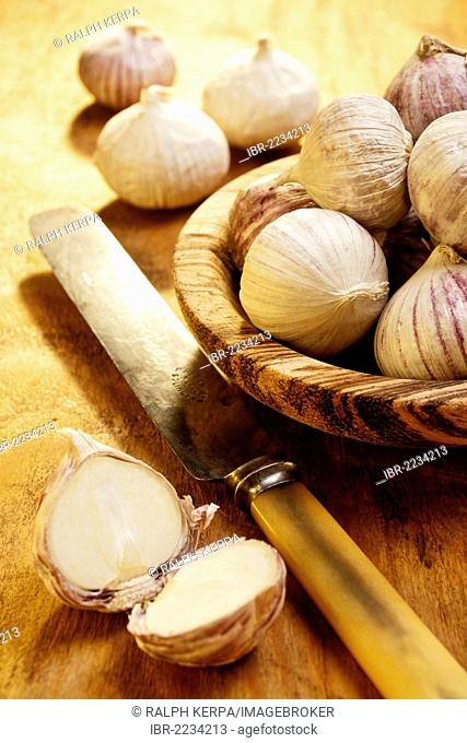 Chinese garlic in a wooden bowl and a knife lying on a table