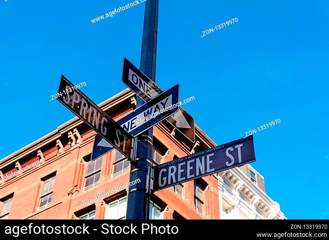 Low angle view of typical building and street name sign in Greene Street and Spring Street in Soho District in New York City