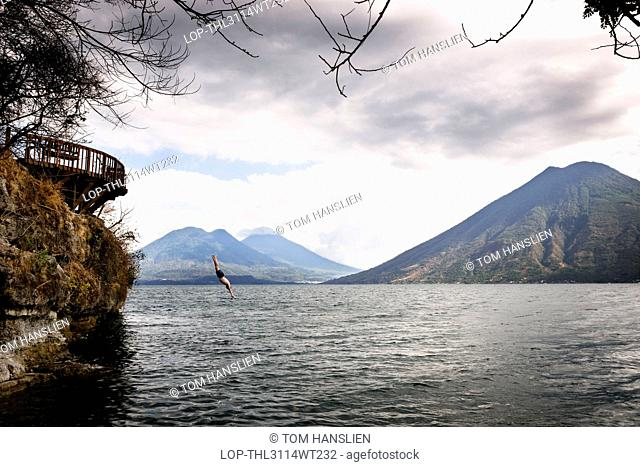 Guatemala, Solola, Lake Atitlan. Diving off a platform into Lake Atitlan
