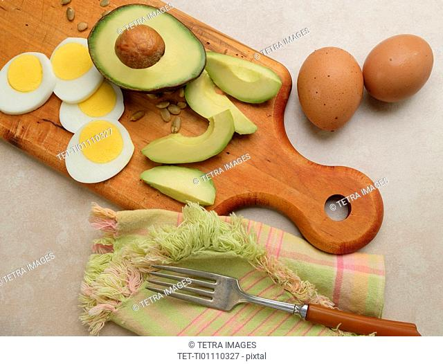 Avocado, egg and sunflower seeds on cutting board
