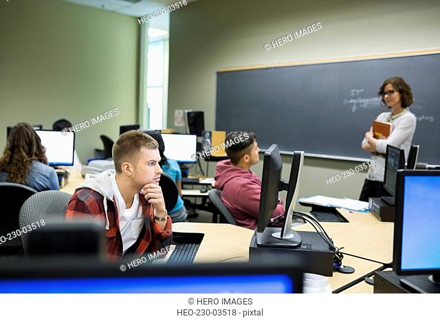 Professor watching college students at computers in classroom