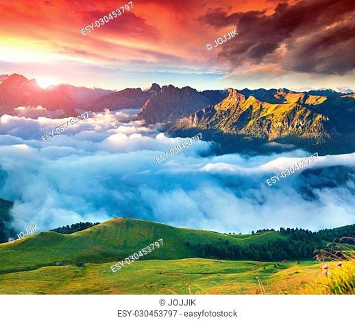 View of the foggy Val di Fassa valley with passo Sella. National Park. Dolomites, South Tyrol. Location Canazei, Campitello, Mazzin. Italy, Europe