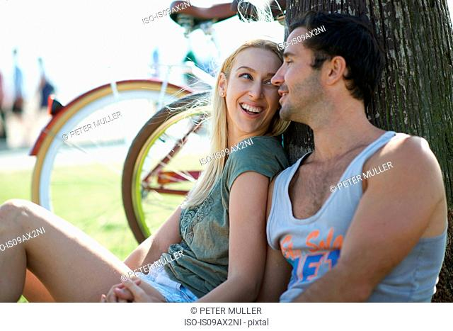 Cycling couple sitting holding hands at Venice Beach, Los Angeles, California, USA