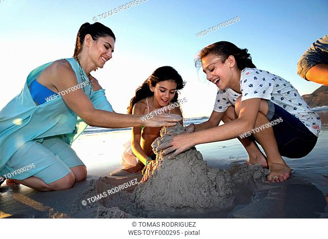 Mother and two daughters building a sand castle on the beach