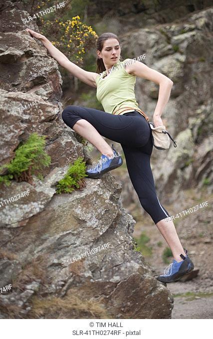 Rock climber scaling boulder