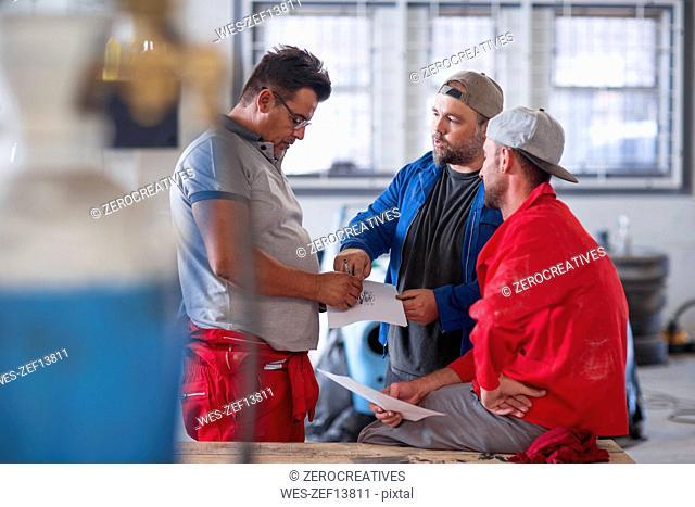 Mechanics restoring vintage cars in workshop