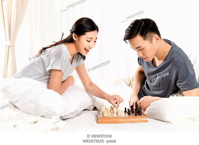 The young couple are playing chess