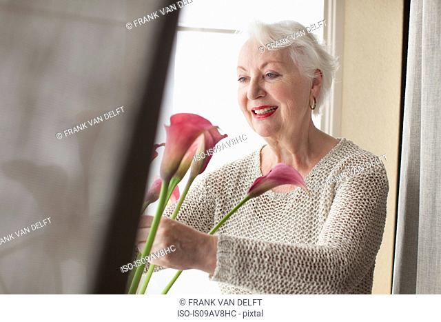 Senior woman arranging flowers ion window sill