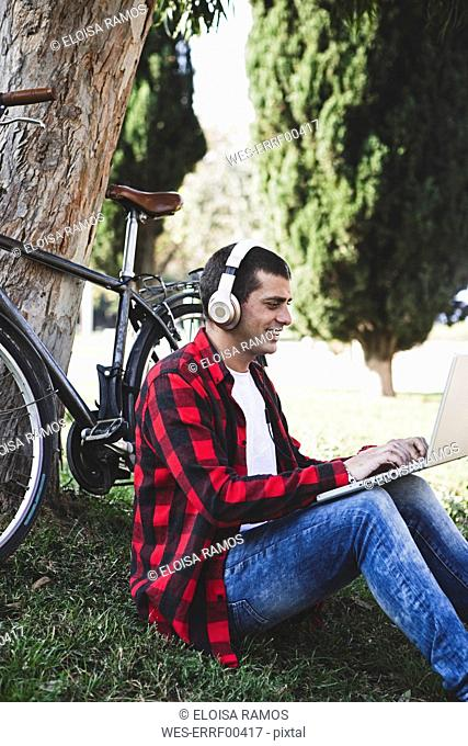 Young man sitting in a park wearing headphones and using laptop next to bicycle