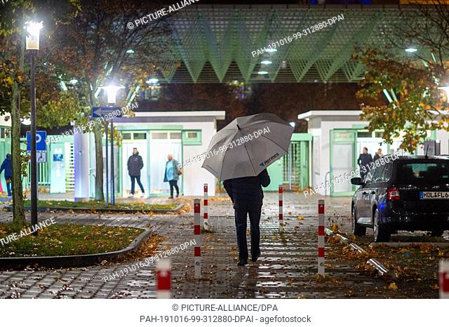 16 October 2019, Saxony-Anhalt, Haldensleben: A man with a Hermes umbrella walks towards the company entrance. After the sudden death of two employees and the...
