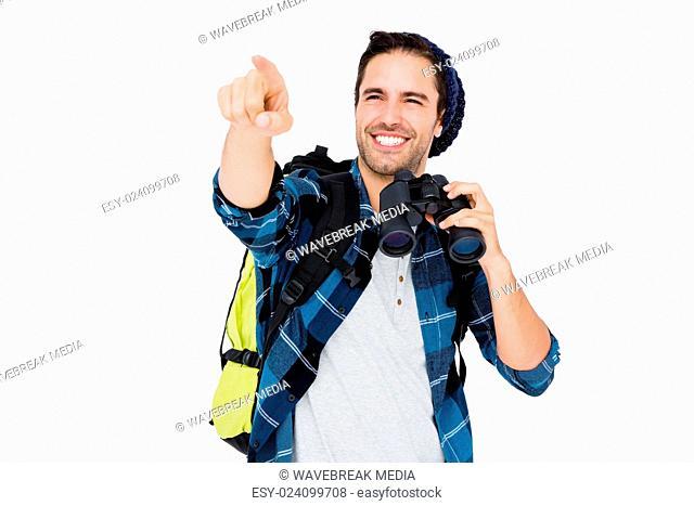Young man carrying rucksack and using camera