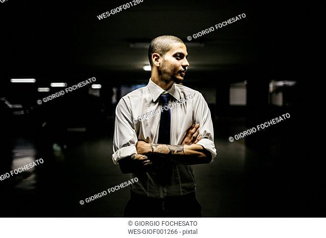 Young businessman with tattoos on his forearms standing in a gloomy car park