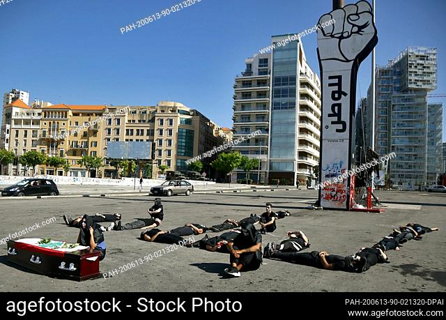 """13 June 2020, Lebanon, Beirut: Anti-government activists form the Arabic letter """"""""Lebanon"""""""" with their bodies as they take part in a symbolic funeral procession..."""