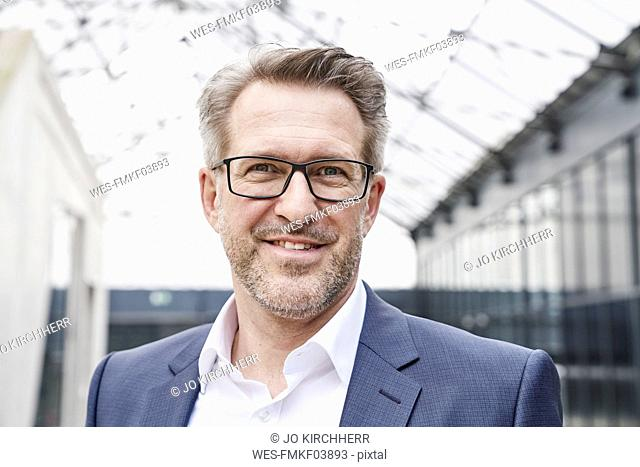 Portrait of smiling businessman with stubble wearing glasses