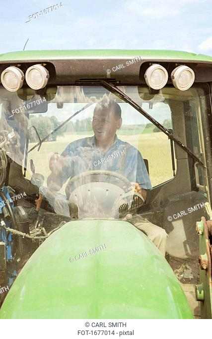 Smiling farmer driving tractor at farm on sunny day
