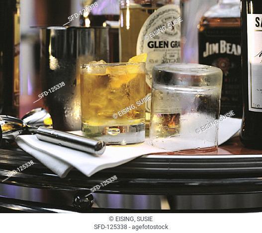 Glen Grant whisky with ice in bar, whisky bottles on bar