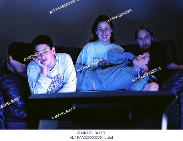 Young adults sitting together on couch watching television in the dark