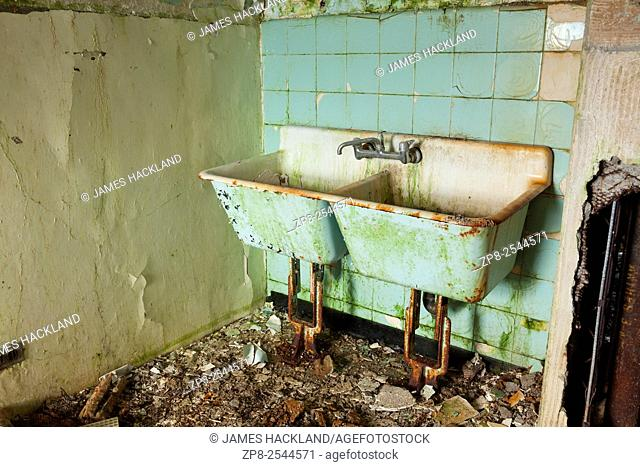 A filthy, rusted old green laundry room sink found in an abandoned hospital in Canada
