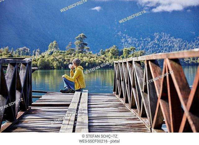 Chile, Chaiten, Lago Rosselot, woman sitting on jetty drinking from mug