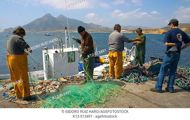 Fishermen cleaning fishing nets. La Isleta del Moro fishing village. Cabo de Gata - Nijar Natural Park. Almeria Province. Andalucia. Spain