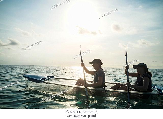 Women in clear bottom canoe on sunny ocean, Maldives, Indian Ocean