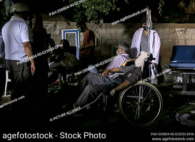 04 August 2020, Lebanon, Beirut: Wounded people receive treatment at the parking lot of Al Roum Hospital, following a a massive explosion in Beirut's port