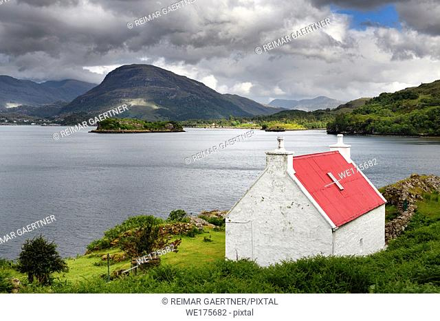 White stone house with red roof on Loch Shieldaig with Eilean an Inbhire Bhain Island and Ben Shieldaig Peak Scottish Highlands Scotland