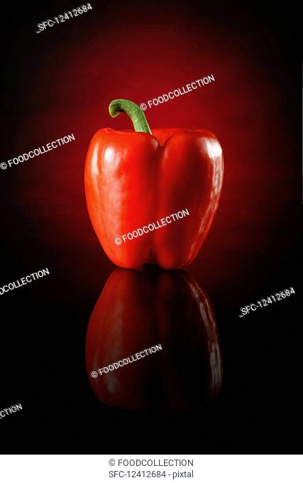 A red pepper against a red and black background