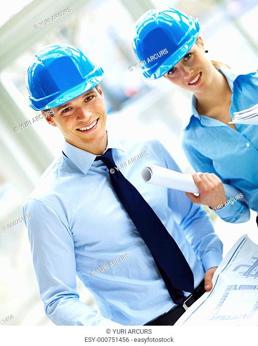 Portrait of contracters in blue helmet with blueprints in their hand