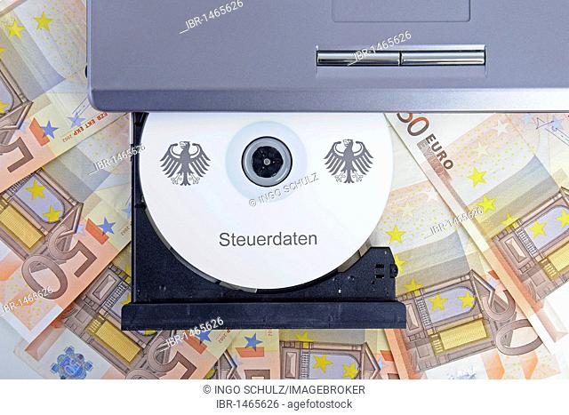 CD labelled Steuerdaten, German for tax data in a computer drive, 50 euro notes, symbolic image for illegal trade with tax data, breach of data protection