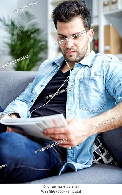 Young man at home with earbuds reading magazine