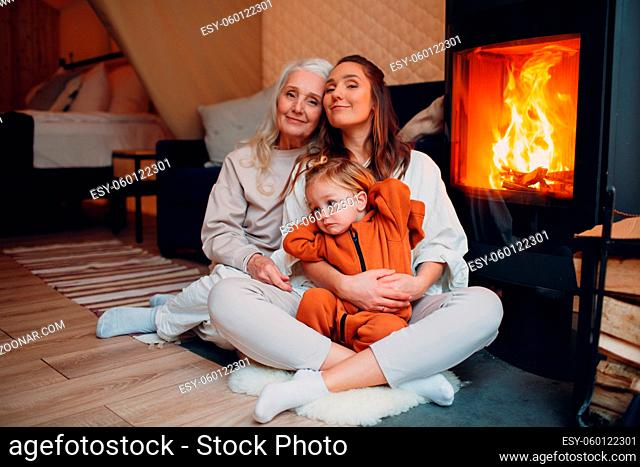 Grandmother, Mother and child sitting and playing on sofa near fireplace. Mom and baby. Parent with daughter and grandson little kid relaxing at home